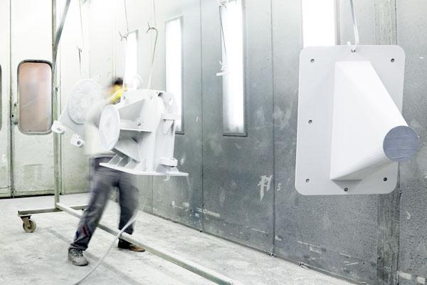 Mitarbeit beim Sandtsrahlen eines Metallstücks – Schuler Dienstleistungen GmbH